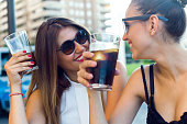 Portrait of beautiful young women drinking refreshment in the street.