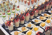 Beautifully multicolored decorated catering banquet table with different food snacks and appetizers with sandwich, caviar, fresh fruits on corporate party event or wedding celebration.
