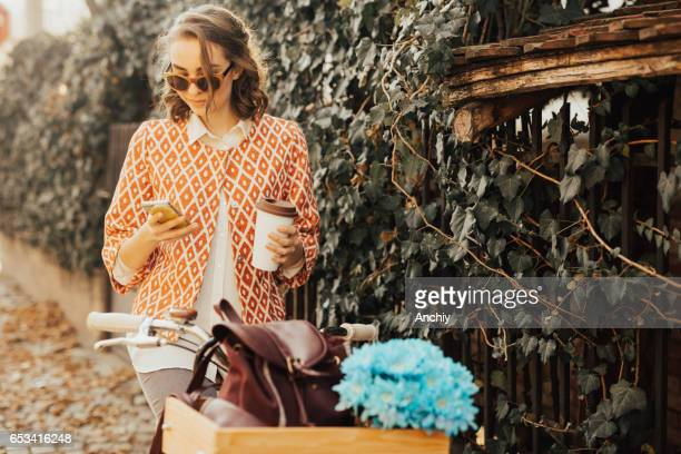 Beautifully dressed girl sitting on the bicycle using smartphone