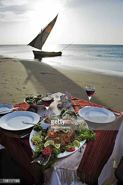 A beautifully prepared sunset romantic seaside fish dinner on the shore at Benguerra Lodge. Traditional dhow or sailing boat in the background. Mozambique . Property released