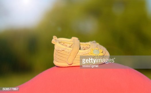 Beauty baby shoes on the mother's belly : Stockfoto