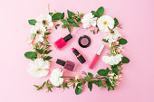 Beauty blogger desk with cosmetics, lipstick, eye shadows, nail polish and pink frame of flowers on pink background. Flat lay, top view.