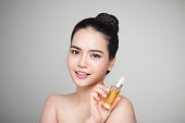 Beauty concept. Asian pretty woman with perfect skin holding oil bottle