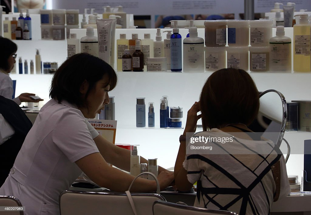 A beauty consultant, left, speaks to a customer in the MT Cosmetics Inc. booth at the Beautyworld Japan fair in Tokyo, Japan, on Monday, May 19, 2014. The business-to-business trade fair hosted by Messe Frankfurt is held through May 21. Photographer: Tomohiro Ohsumi/Bloomberg via Getty Images