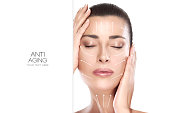 Head shot of beautiful model with hands on face and closed eyes with a serene expression suitable for anti aging treatment and plastic surgery concept.  Portrait isolated on white with copy space for