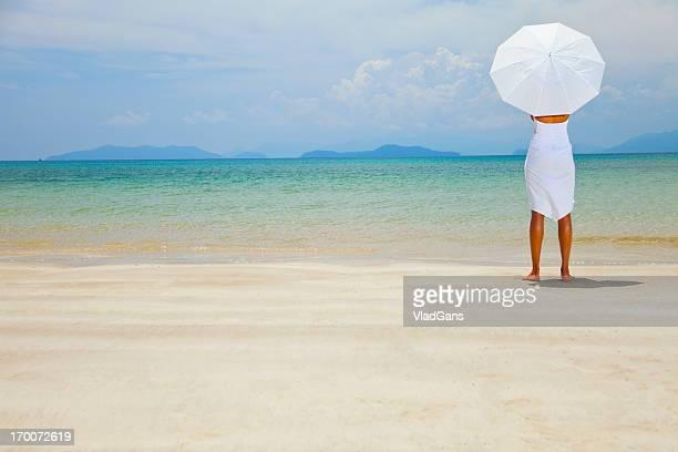 美しさの女性のホワイトドレスで、海を背景に