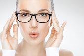 Beauty headshot of beautiful woman holding eyeglasses and blowing kisses