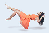 Full length studio shot of attractive young woman in orange dress hovering in air and looking surprised