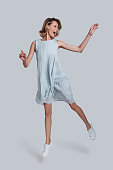 Full length of playful young woman gesturing and keeping mouth open while jumping against grey background