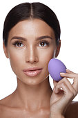 Beauty Makeup. Portrait Of Beautiful Sexy Woman Applying Foundation With Cosmetic Blender Sponge. Portrait Of Young Female With Pure Fresh Skin And Perfect Facial Makeup. Cosmetics. High Resolution