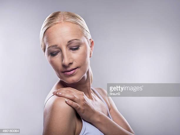 Beauty mature woman touching her soft skin.