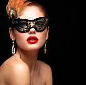 Beauty model woman wearing venetian masquerade carnival mask at party isolated on black background. Christmas and New Year celebration. Glamour lady with perfect make up