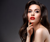 Beauty Model Woman with Long Brown Wavy Hair. Healthy Hair and Beautiful Professional Makeup. Red Lips and Smoky Eyes Make up.