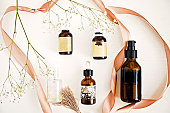 Organic Maroccan argan, rose and almond oils in dark bottles. White background. Beauty blogger flat lay concept
