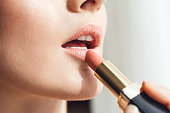 Close up detail of young woman with nice clean and soft skin applying red lipstick on her perfect sexy plump lips.