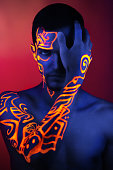 Creative man model shine blue orange colors. Bright conceptual art make-up body-art glows under ultraviolet light. Club disco neon party time. Drink alcohol feel wild energy of music. Halloween horror