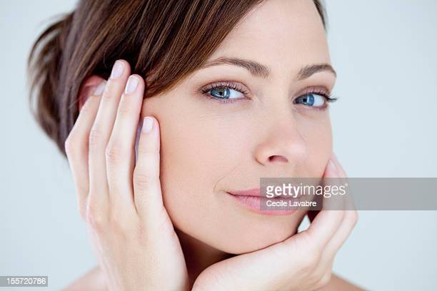 Beauty portrait of a woman with hands to her face