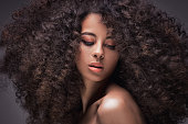Beauty portrait of sensual african american woman with long curly hair .
