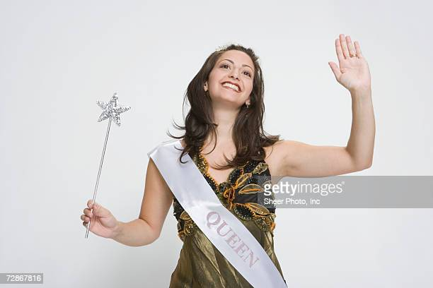 Beauty queen waving hand, holding magic wand, smiling