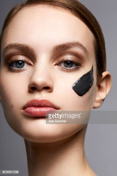 Beauty shot of a young woman with charcoal cream spot on her cheek