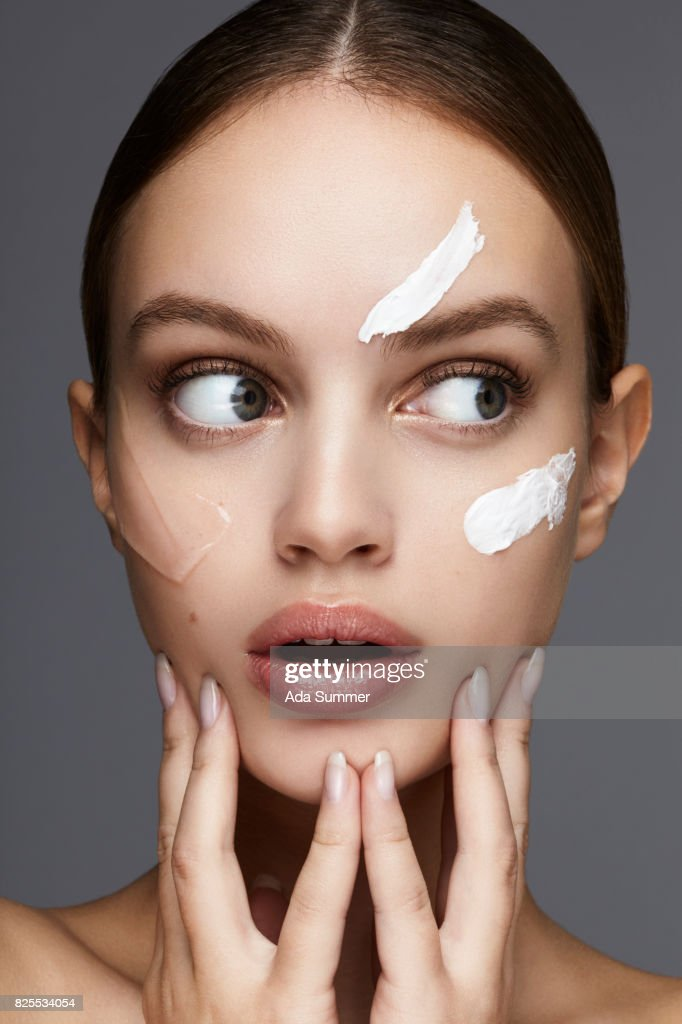 Beauty shot of a young woman with lotion on her cheek : Stock Photo