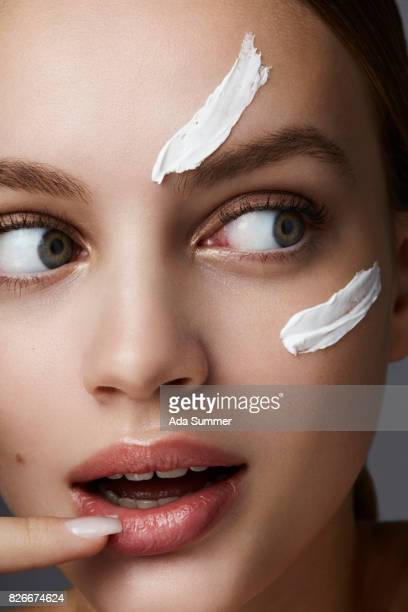 Beauty shot of a young woman with lotion on her cheek