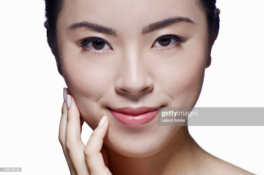Beauty shot of Asian woman with hand to face : Stock Photo