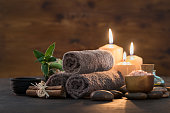 Brown towels with bamboo and candles for relax spa massage and body treatment. Beautiful composition with candles, spa stones and salt on wooden background. Spa and wellness setting ready for beauty t