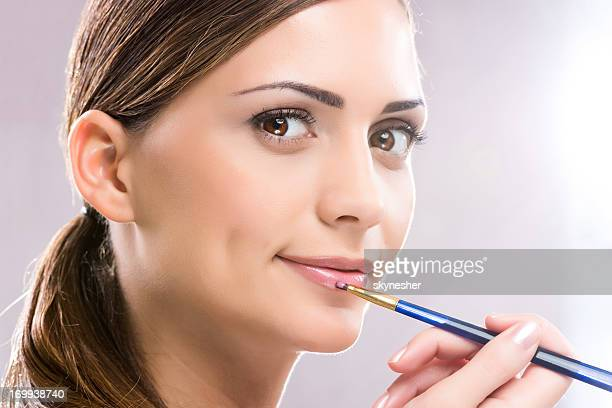 Beauty woman applying lipstick.