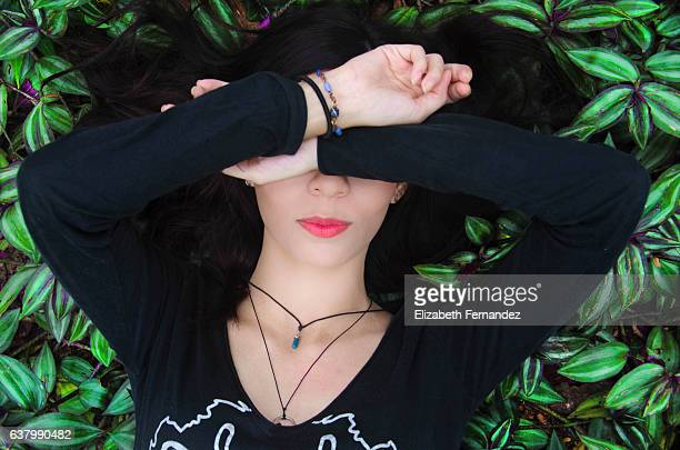 A beauty young woman lying down on lush foliage