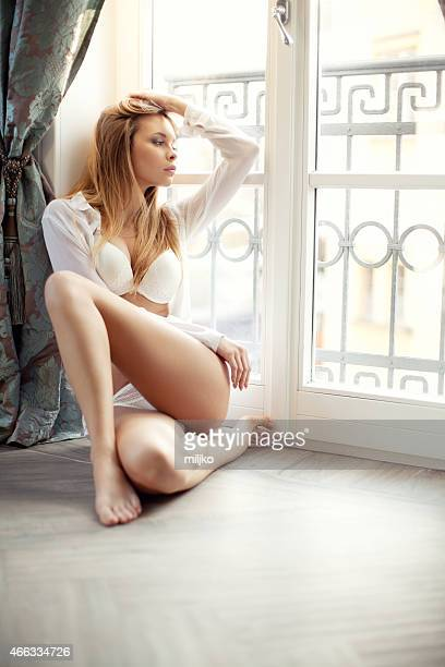 Beautyful young blond woman sitting next to the window
