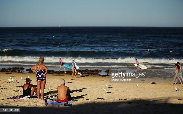Becahgoers watch young surfers at Coogee beach on February 25 2016 in Sydney Australia The bureau of meteorology forecast temperatures over 40...