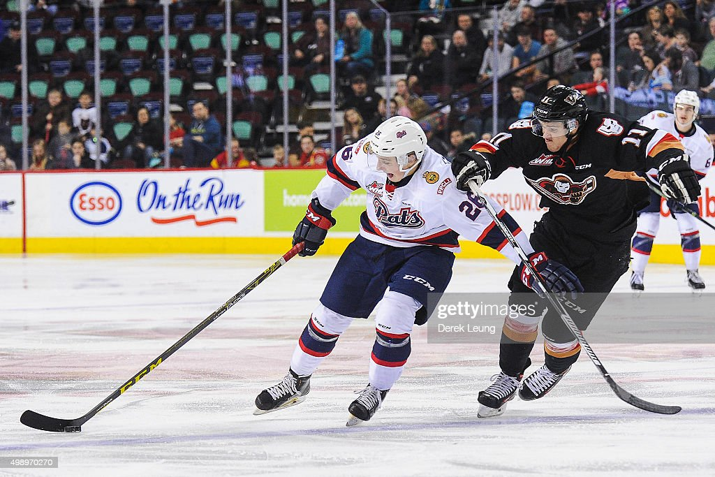 Beck Malenstyn #11 of the Calgary Hitmen chases Jake Leschyshyn #26 of the Regina Pats during a WHL game at Scotiabank Saddledome on November 27, 2015 in Calgary, Alberta, Canada.