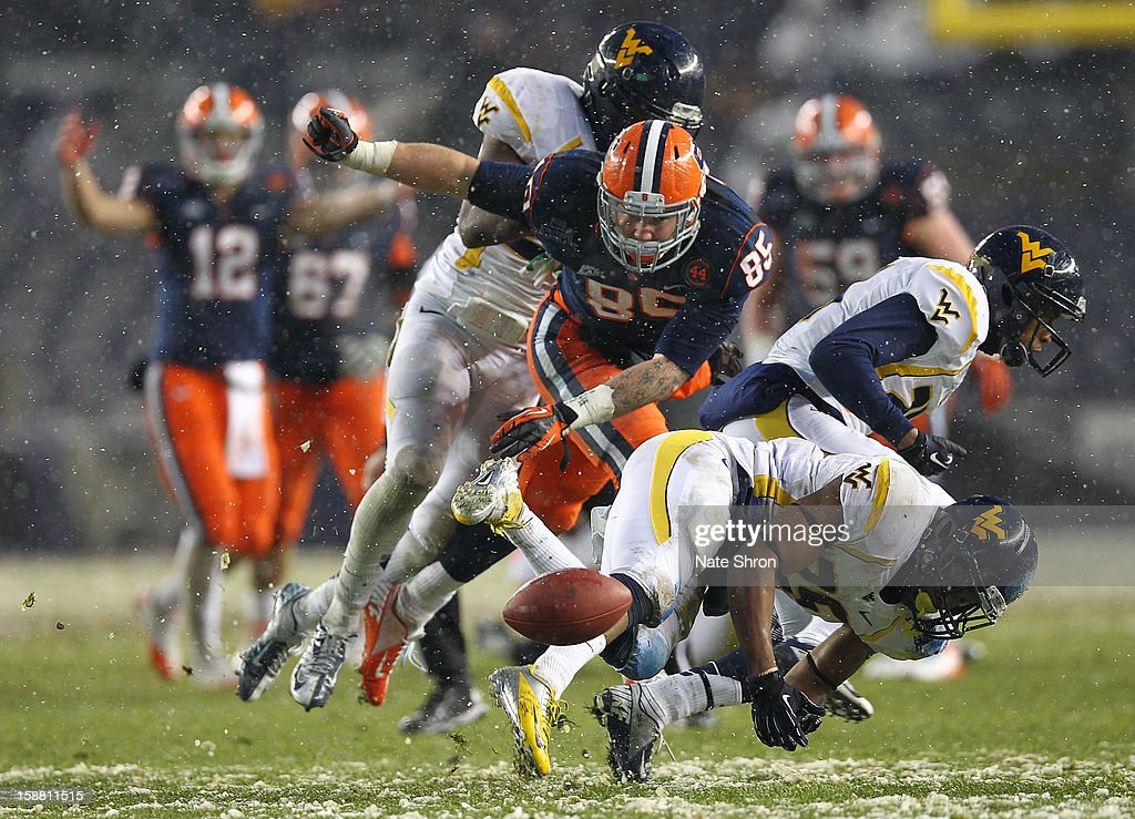 Beckett Wales #85 of the Syracuse Orange reaches for the ball against Cecil Level #24 and Darwin Cook #25 of the West Virginia Mountaineers during the New Era Pinstripe Bowl at Yankee Stadium on December 29, 2012 in the Bronx borough of New York City.