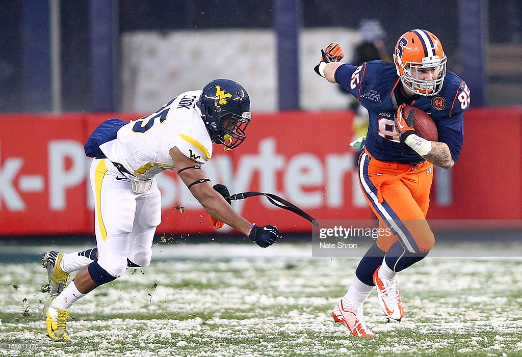 Beckett Wales #85 of the Syracuse Orange runs the ball against Darwin Cook #25 of the West Virginia Mountaineers during the New Era Pinstripe Bowl at Yankee Stadium on December 29, 2012 in the Bronx borough of New York City.