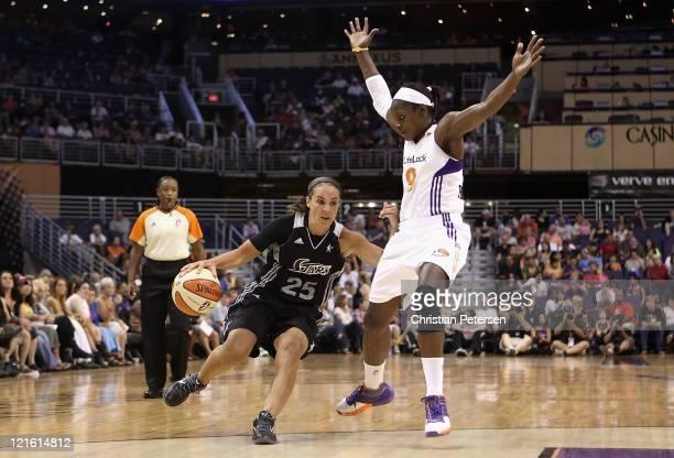 Becky Hammon of the San Antonio Silver Stars handles the ball under pressure from Marie FerdinandHarris of the Phoenix Mercury during the WNBA game...