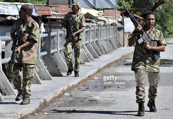 East Timorese government soldiers walk back to their barracks from the mountain near Becora outskirts of Dili to take a break during clashes with...