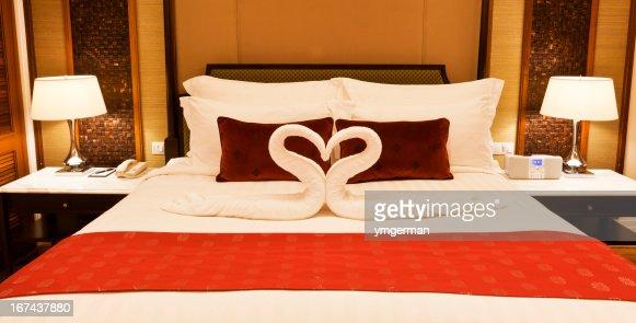 Cama no quarto de hotel com toalhas formação de forma de coração : Foto de stock