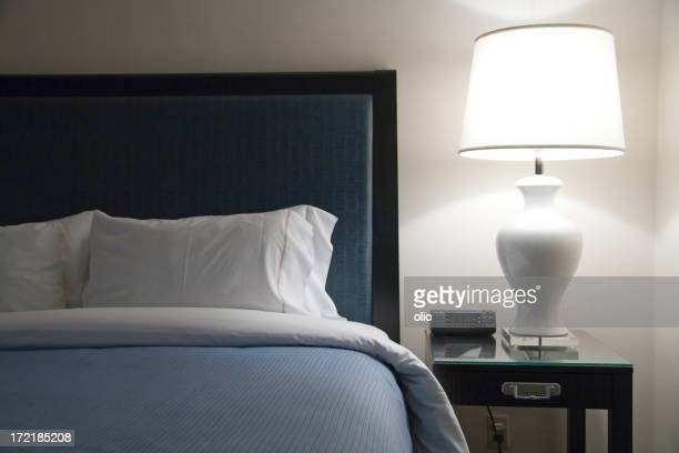 Bed of modern hotel with blue accents next to a lot lamp
