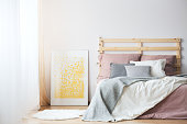 King-size bed, yellow poster and white rug in cozy bedroom