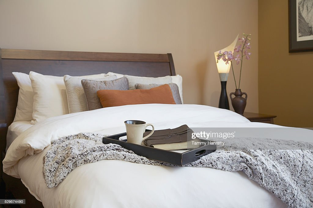 Bed with coffee cup and book on tray : Stock Photo