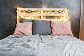 Cozy dreamy bed with decorated DIY pallet headboard