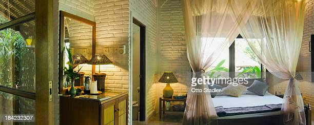 Bed with mosquito net in tropical beach bungalow