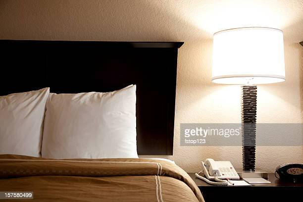 Bed with pillows, end tables and duvet. Hotel room. Lamp.