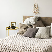 Bed with wooden headboard, pillows, knitted blanket. Scandinavian interior