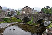 Stone bridge and the River Glaslyn, Afon Glaslyn, at the centre of Beddgelert village in Snowdonia, Gwynedd, Wales, UK.