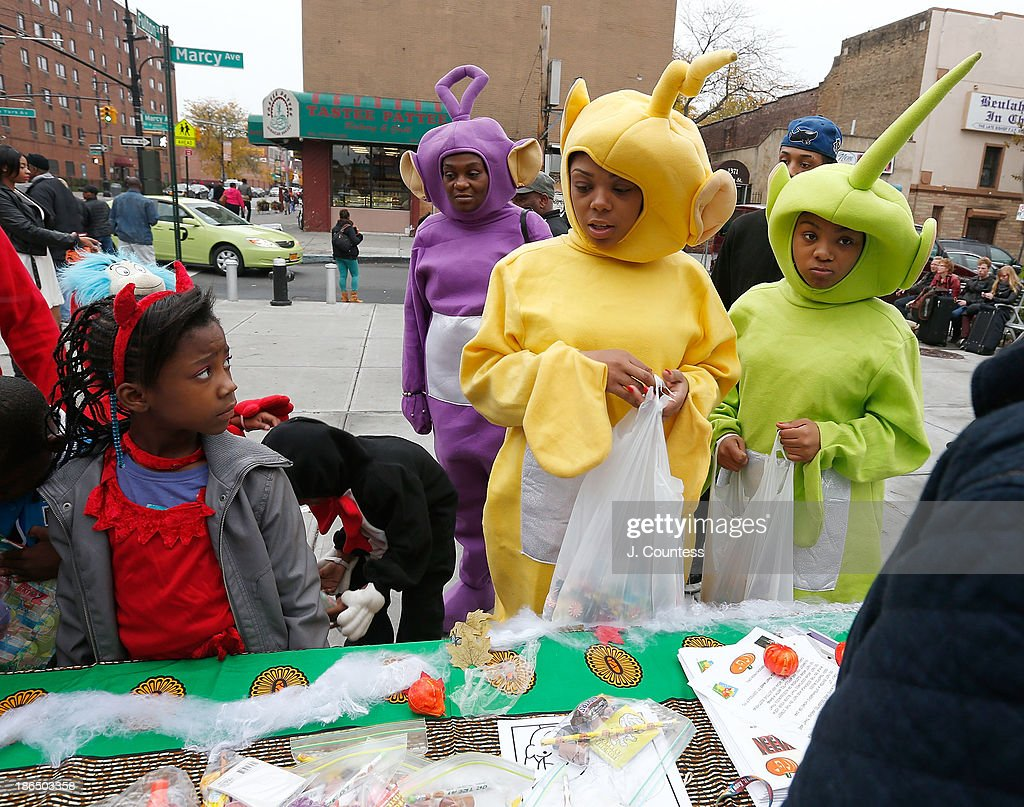 Bedford-Stuyvesant residents collect candy and books offered by the Brownstoners of BedfordÐStuyvesant Organization on October 31, 2013 in New York City.