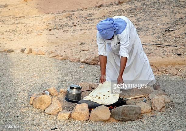 Bedouin baking bread on hot stone, Sinai Desert,Egypt