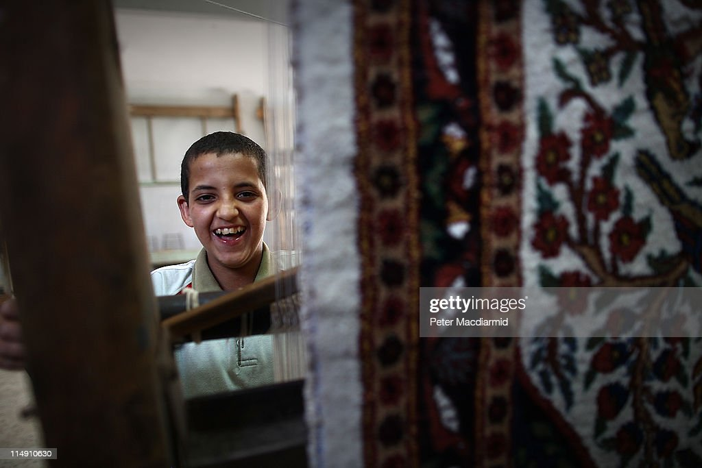 Bedouin boy Ramadan, aged 14, smiles as he weaves a carpet at a government run carpet school on May 28, 2011 in Sakara, Egypt. Protests in January and February brought an end to 30 years of autocratic rule by President Hosni Mubarak who will now face trial. Food prices have doubled and youth unemployment stands at 30%. Tourism is yet to return to pre-uprising levels.