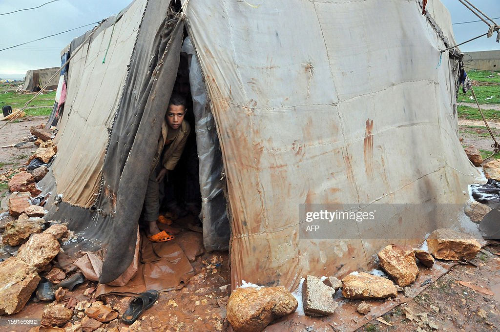 A Bedouin child from Syria, who has taken refuge with his family for the winter in Lebanon, stands inside a tent close to the village of Kfarkahel, in the Koura district near the northern city of Tripoli on January 9, 2013, as stormy weather sparked widespread flooding, prompting chaos on the roads and a nationwide school closure. The number of Syrian refugees in Lebanon is already totaling 156,000, according to UN figures, and 200,000 according to the Lebanese government estimates. AFP PHOTO/IBRAHIM CHALHOUB